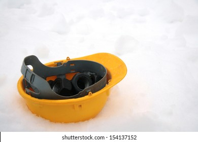 Yellow building helmet on snow as container for nuts