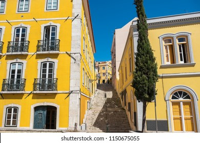 Yellow buildings and stairs on a Travessa Arrochela street. Sao Bento, Lisbon, Portugal