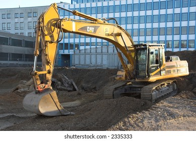 Yellow bulldozer against office-building