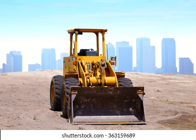 A yellow bulldozer is in a construction site with a city buildings background