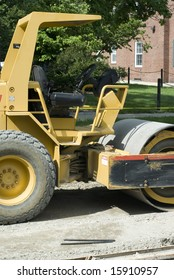 A yellow bulldozer idles on a road.