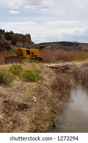 Yellow bulldozer next to an agricultural irrigation ditch with high water - wide vertical orientation.