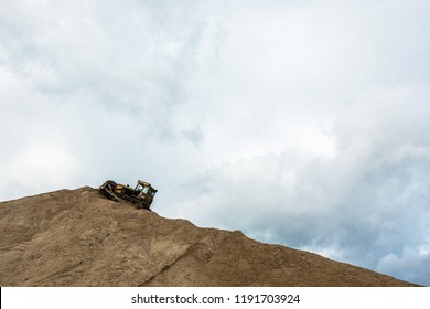Yellow bulldozer on a large hill of sand on the background of the cloudy sky.