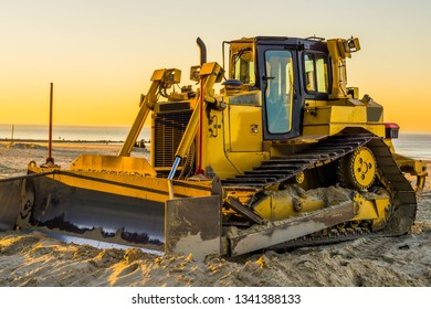 yellow bulldozer with a scoop at sunset on the beach, ground moving equipment, groundwork industry