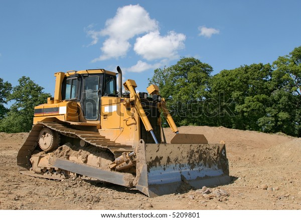 Yellow bulldozer standing idle on rough earth with trees and a blue sky to the rear.