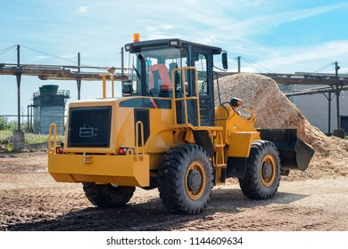Yellow bulldozer works at woodworking plant. Heavy wheel loader, tractor, machinery, industrial vehicle