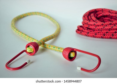A yellow bungee cord with red hooks next to a coil of red and black rope, on a plain background