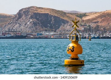 Yellow buoy in the Port of Ensenada in Baja California, Mexico with the city and mountains in the background.