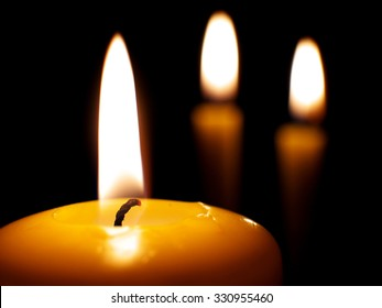 yellow burning candles on dark background, macro