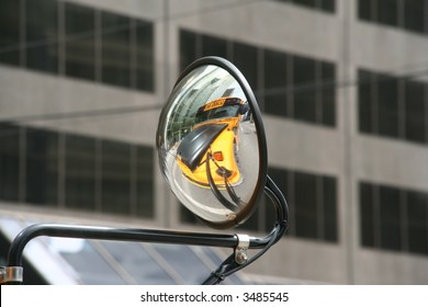 yellow bus in convex mirror or concave reflection of school busses
