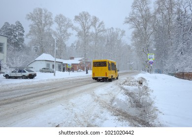 Yellow bus on the background of snow-covered roads.