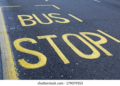 Yellow bus stop sign at asphalt