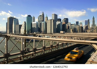 Yellow Cab driving over Brooklyn Bridge with New York City skyline in the background