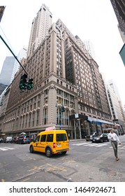 Yellow cab and street signs in front of a big office building on madison avenue in New York City, United States of America, july 25 2019