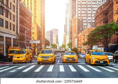 Yellow cabs waiting for green light on the crossroad of streets of New York City during sunny summer daytime