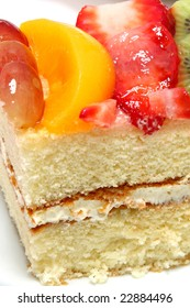 Yellow cake with fruit glaze and fresh strawberry, kiwi, grape and peach on top.
