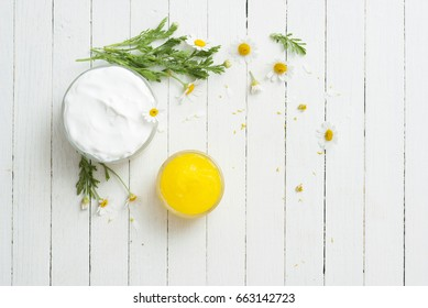 yellow calendula medical cream and white moisturizer with flowers on bright wooden table background