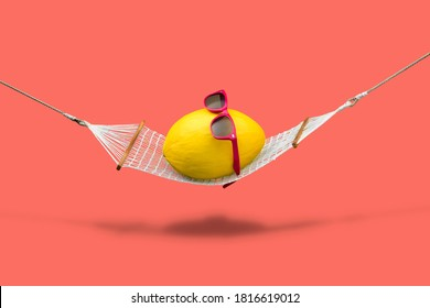 Yellow canary melon with red sunglasses relaxing in hammock on pink background. Vacation or wellness concept.