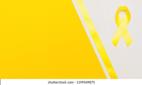 yellow cancer awareness ribbon with trail on white background. concept of health and medicine