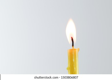 yellow candle flame straight on white background
