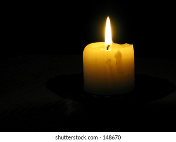 A yellow candle lit in a very dark room,You can only see the top part of the candle and the flame,