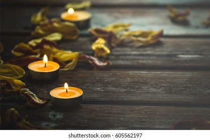 yellow candles and dried flower petals on wooden boards