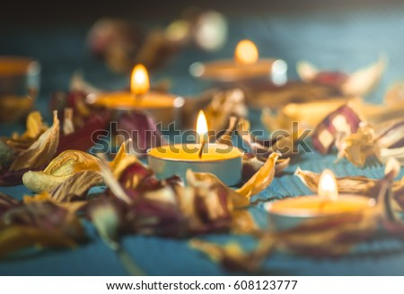 yellow candles and plamennoi surrounded by dry petals of tulips on blue wooden boards