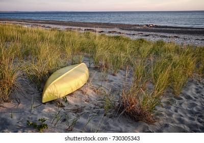 Yellow Canoe on empty Beach at Ocean at Dawn