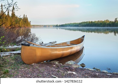 Yellow canoe on the shore of a calm northern Minnesota lake in early morning light