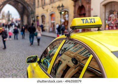 Yellow car with taxi sign on the roof waiting in old town of Prague, Czech Republic (focus on the sign).
