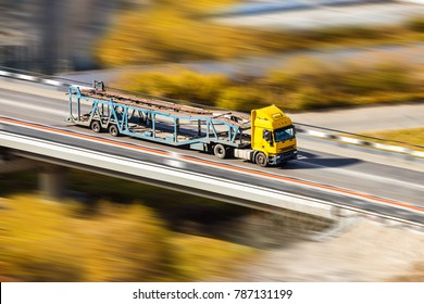Yellow car transporter moving fast at the bridge in autumn