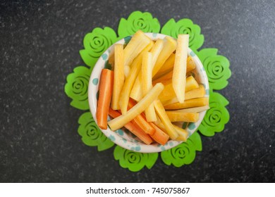 Yellow carrots in a white plate with a green pad on a dark background.