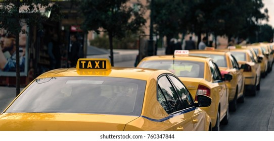 yellow cars of the taxi stand in one row on the city street