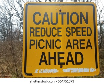 yellow caution reduce speed picnic area head sign next to bike trail