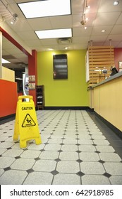 A yellow caution sign warning of slippery wet floors sits on the tile floor of a restaurant