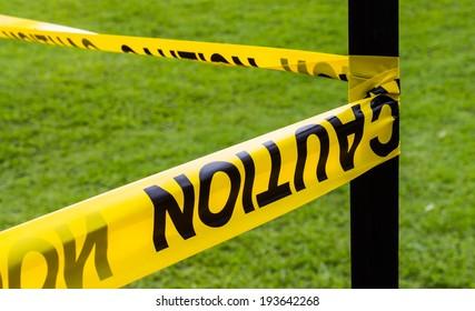 Yellow caution tape bind to a black pillar
