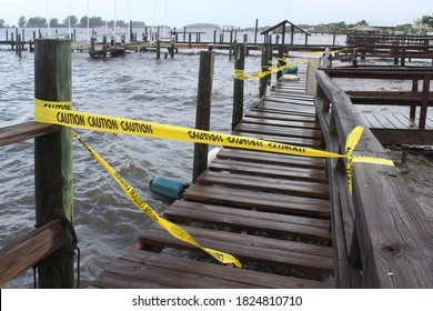 Yellow caution tape blocking off access to a public dock at a local marina due to damage from waves crashing in to the wooden dock boards during a bad storm.