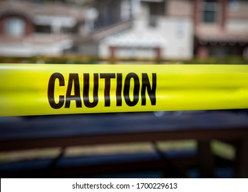 Yellow caution tape in english and spanish barring access to playgound equipment at a park. The access is denied due to the Coronavirus Pandemic but the image could be used for other situations