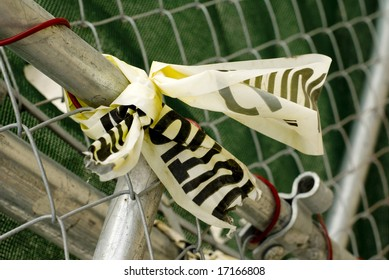 Yellow caution tape on metal fence