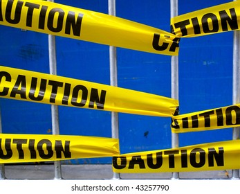 Yellow caution tape on a metal barrier