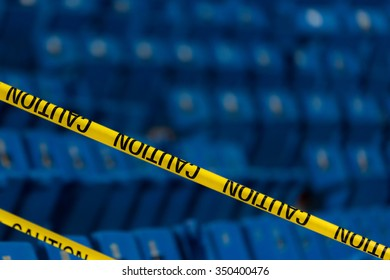Yellow caution tape in a stadium. There are blue seats in the background. Room for text above.