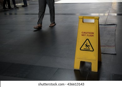 Yellow caution Wet Floor sign with blur background leg of people is walking.