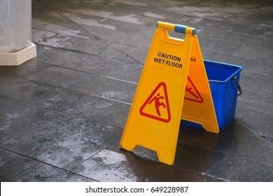 Yellow Caution wet floor sign on wet floor with blue bucket