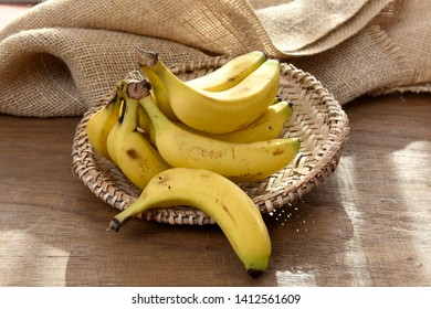 The yellow cavendish banana in a small basket on a wooden table