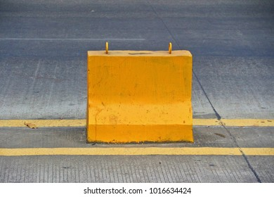 Yellow cement barrier in the middle of road