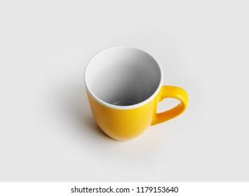 Yellow ceramic cup or mug for coffee or tea.