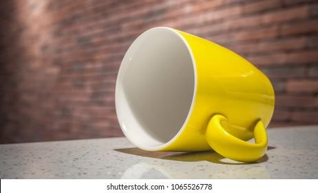 Yellow ceramic mug lying on its side on a blurry brick wall background