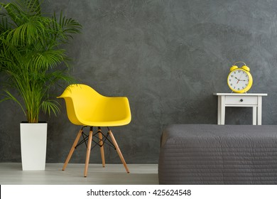 Yellow chair and clock alarm and green plant in dark grey bedroom