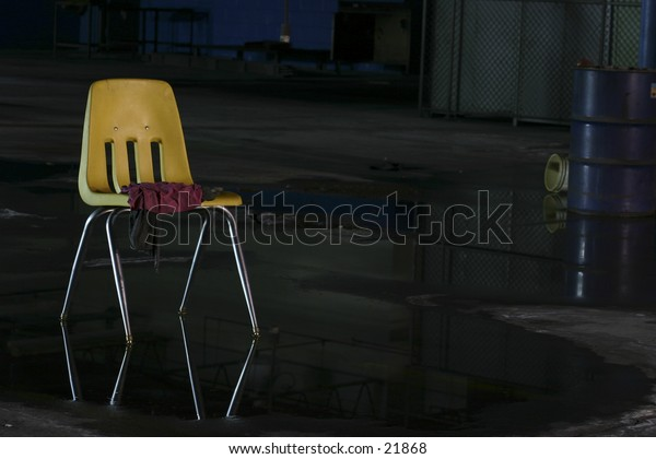 Yellow chair stands boldly against dark, wet abandoned factory.