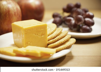 Yellow cheddar cheese is sliced on a white plate with round crackers.  Another plate of red seedless grapes sits in the background along with two red Gala apples.